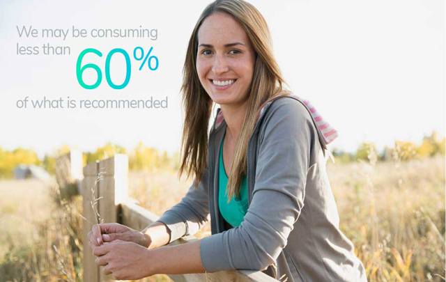 Woman smiling and leaning on fence in countryside.