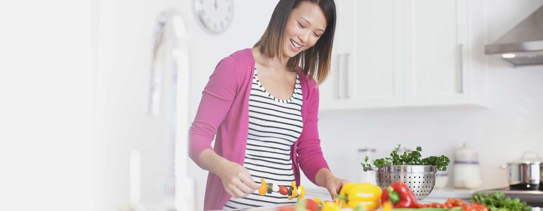 Woman preparing food in kitchen with Skybright Organic Apple Cider Vinegar.