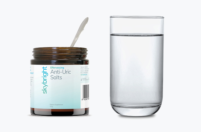 Skybright Anti-Uric Salts next to a glass of water.