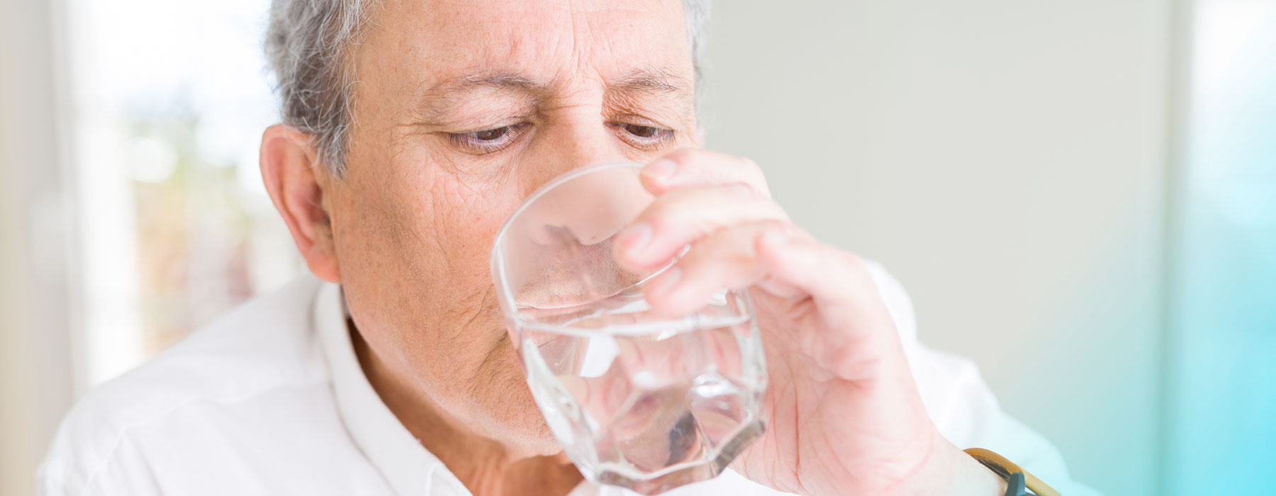 Man drinking Skybright Anti-Uric Salts from a glass of water