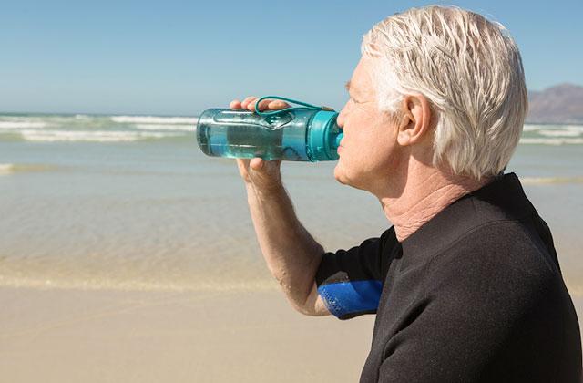 Man drinking water from water bottle.