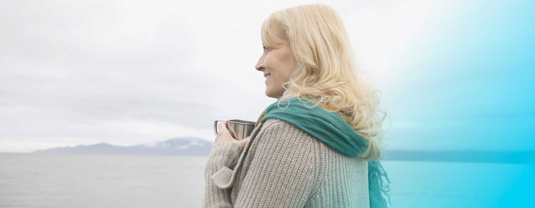 Woman holding mug and looking out to sea. Are you getting enough iodine?