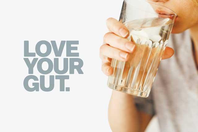 Woman drinking Organic Apple Cider Vinegar daily tonic. Love your gut