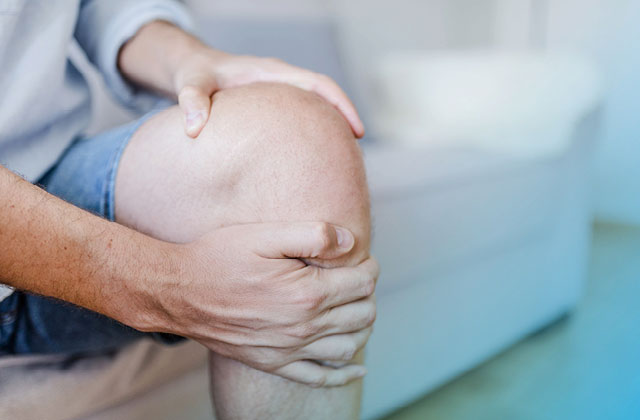 Man clutching knee with inflammation.