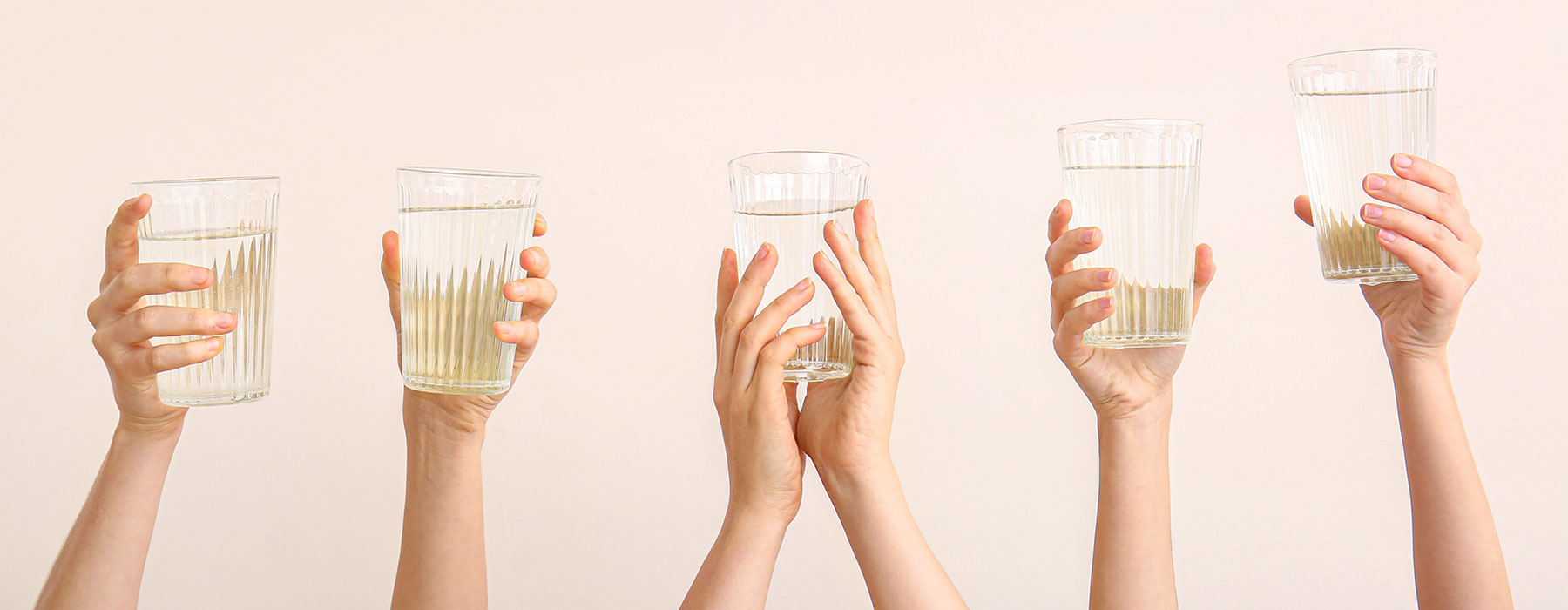 People holding up glasses of water containing Organic Apple Cider Vinegar.